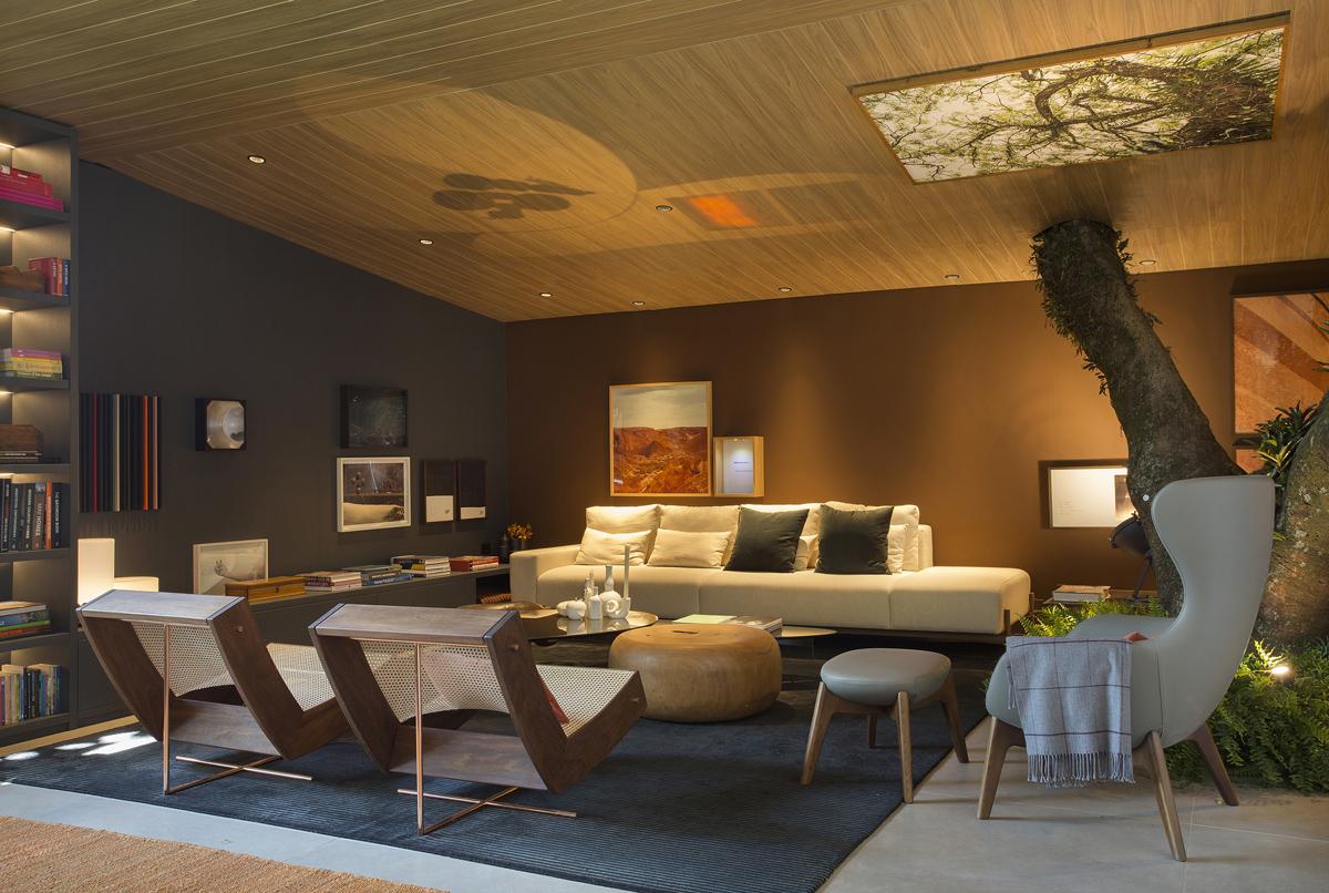 Phòng khách kết nối trực tiếp và thú vị với thiên nhiên thông qua cây lớn mọc xuyên trần nhà, ngay cạnh bộ ghế sòa màu trắng trang nhã.