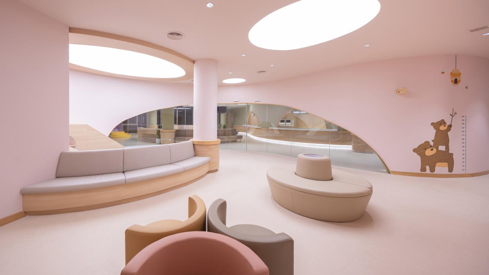 Phòng chờ màu hồng có khu vui chơi và ghế dài êm ái cho trẻ nghỉ ngơi, thư giãn.