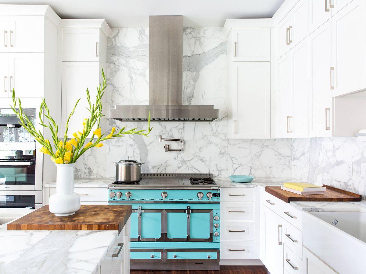 Sắc xanh ngọc lam và bình hoa tươi màu vàng là sự bổ sung hoàn hảo cho phòng bếp  sắc trắng tinh khôi chủ đạo.