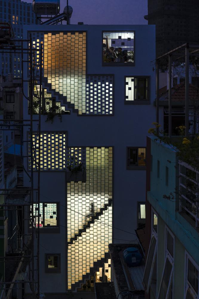 Khung cảnh nhà phố Sài Gòn về đêm với ánh sáng đèn ấm áp phản chiếu qua tường gạch kính trông thật lung linh, huyền ảo.