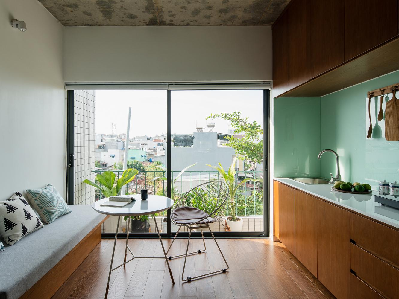 phòng khách và bếp ăn trong căn hộ cho thuê, cửa kính lớn mở ra ban công lấy sáng