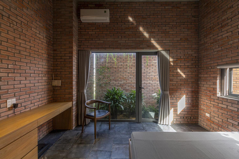 Một góc phòng ngủ với giường, ghế ngồi đọc sách, kệ gỗ, tường gạch, cửa kính mở ra sân vườn