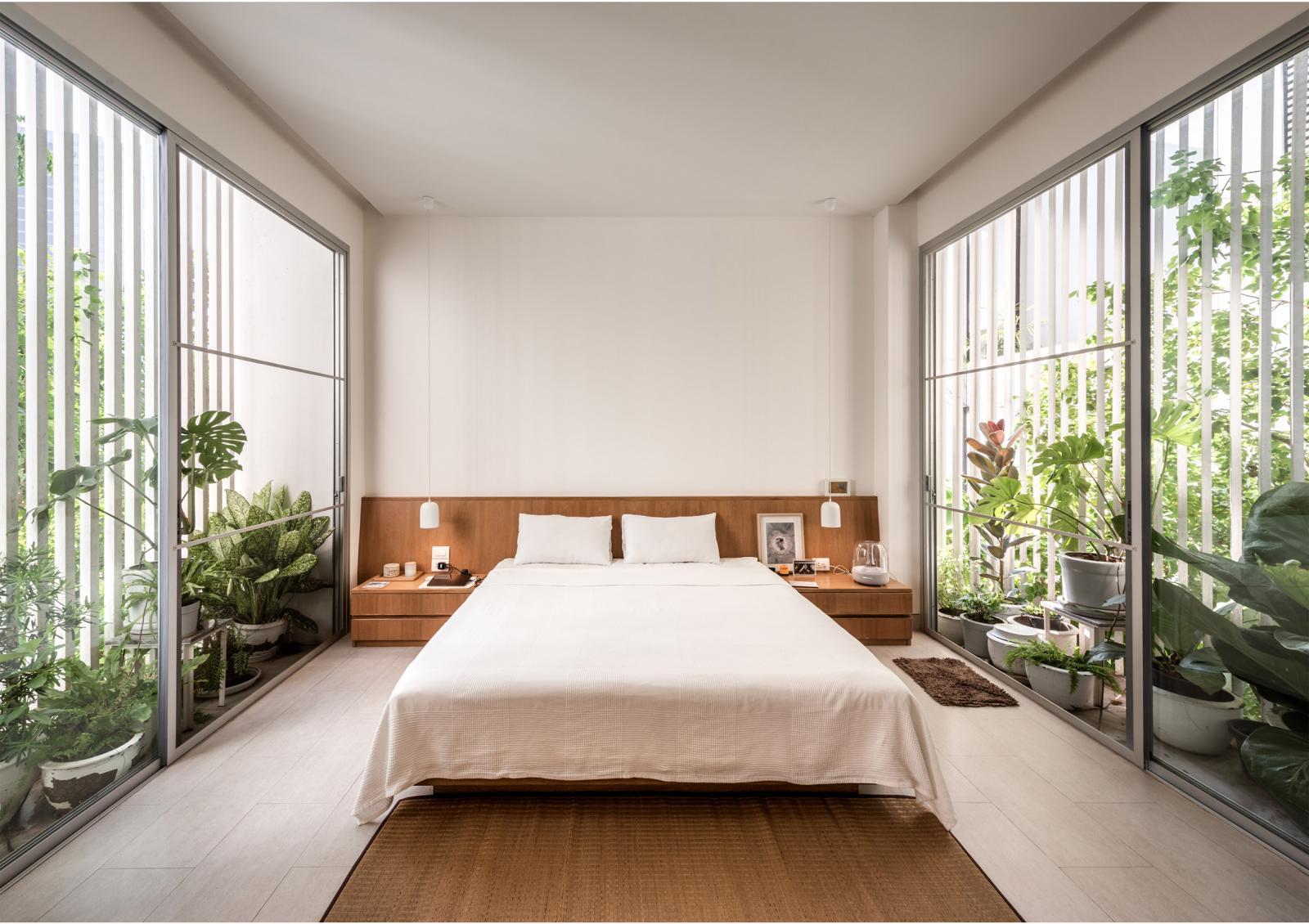 Hai ban công dài và hẹp bao quanh phòng ngủ chính được lấp đầy bởi những chậu cây xanh tốt. Hệ cửa kính trong suốt lấy sáng tự nhiên và thông gió tối ưu cho căn phòng.