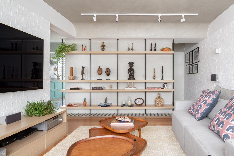góc phòng khách với tivi gắn tường, bàn trà gỗ, kệ bày đồ trang trí, sofa xám