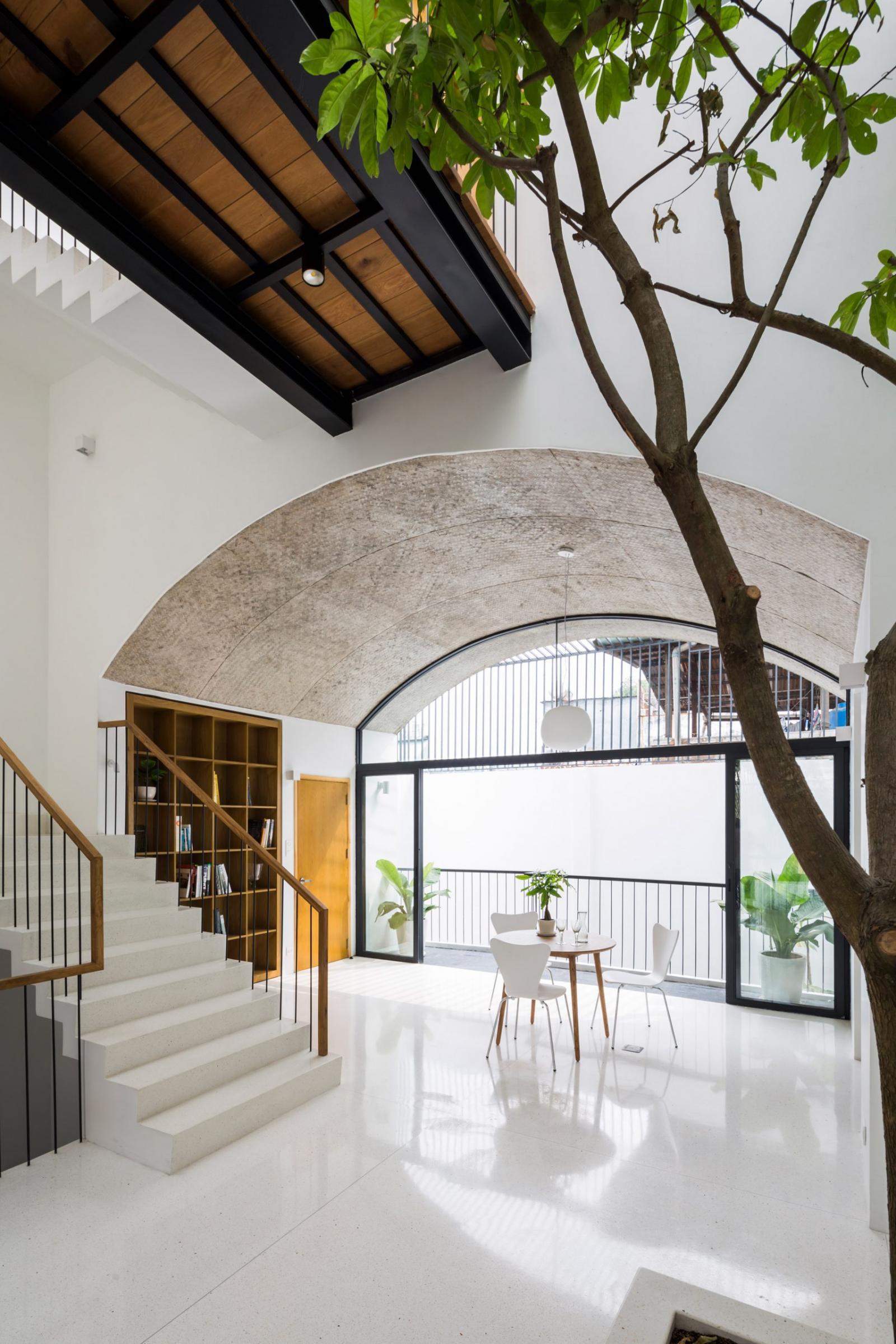 Kiến trúc mái vòm cao rộng ở tầng một tạo cảm giác thoáng rộng cho khu vực thư viện mini và cây xanh trong nhà.