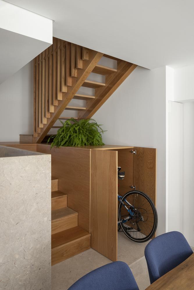 Gầm cầu thang được thiết kế thành nơi cất gọn chiếc xe đạp.