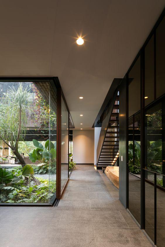hình ảnh khu vực hành lang biệt thự với sân vườn xanh mát, cầu thang bậc hở, vách kính trong suốt