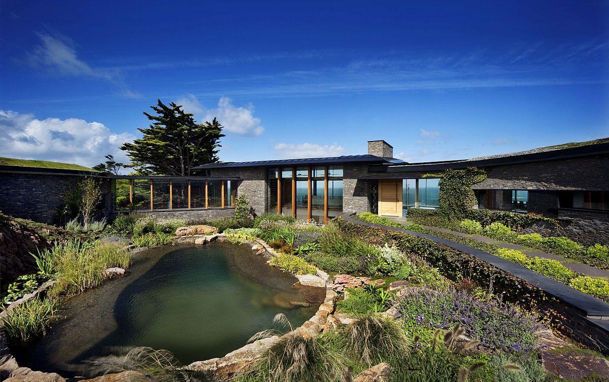 Khuôn viên ngoại thất ngôi nhà với hồ nước tự nhiên và những cây bụi thấp.