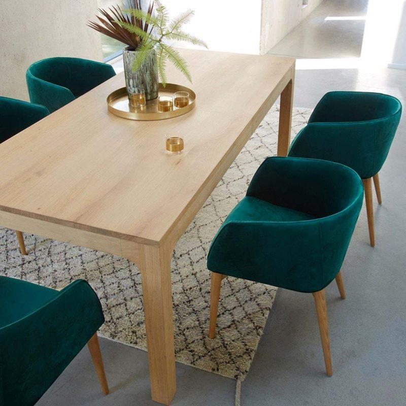 hình ảnh phòng ăn với bàn gỗ dài, ghế bọc nệm màu xanh cổ vịt, khay đĩa bằng đồng, thảm trải màu xám