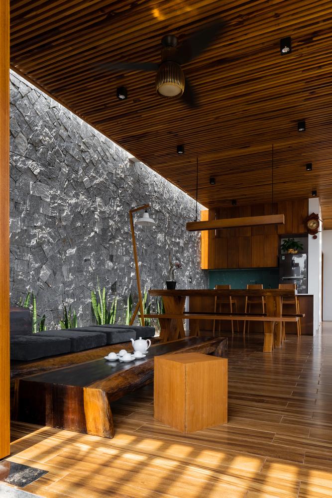 toàn cảnh không gian sinh hoạt chung trong nhà cấp 4 với trần ốp gỗ, bàn ghế gỗ