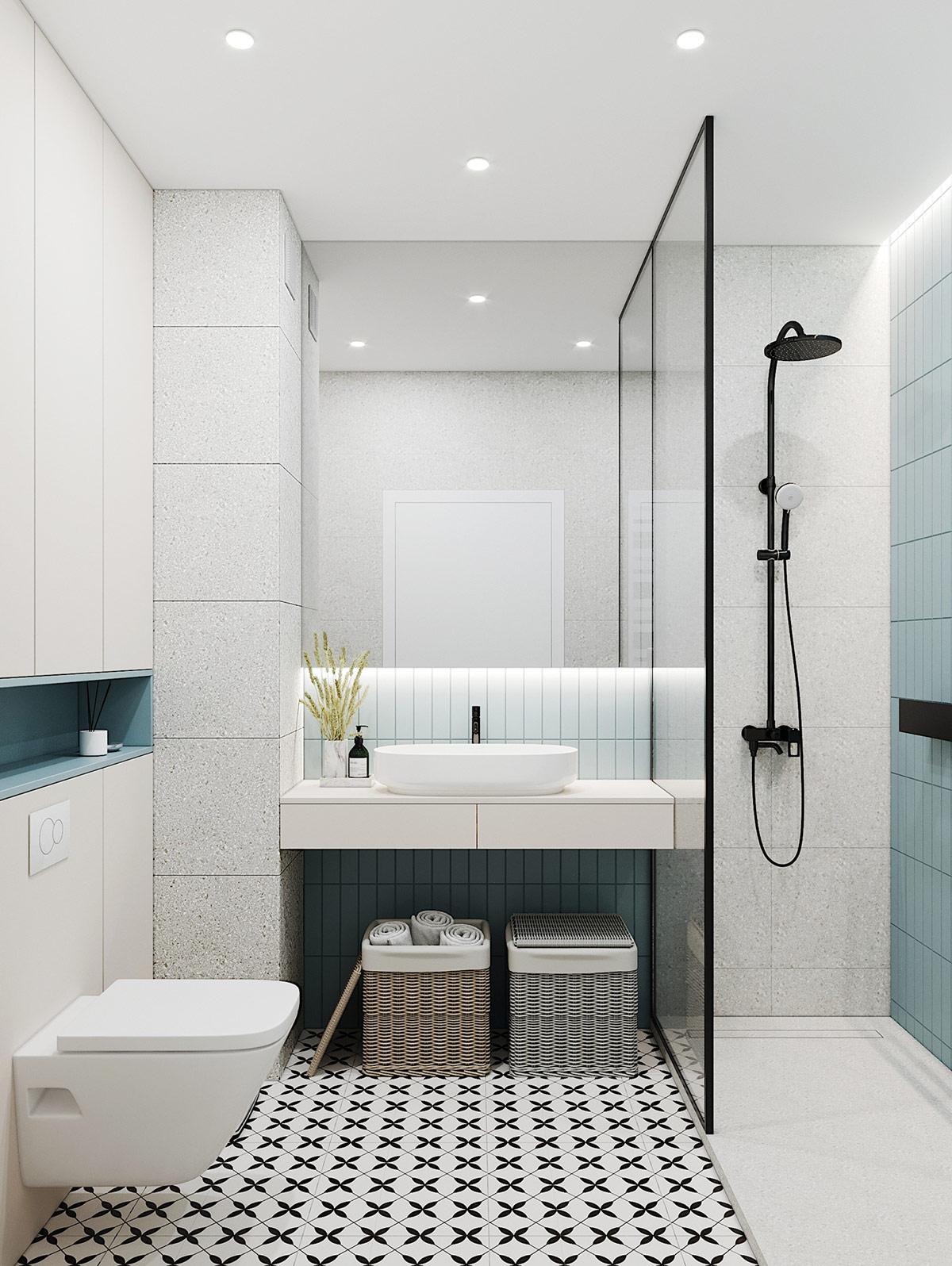Giỏ đựng quần áo bằng mây hình vuông tận dụng không gian trống bên dưới bàn trang điểm nổi trong phòng tắm.