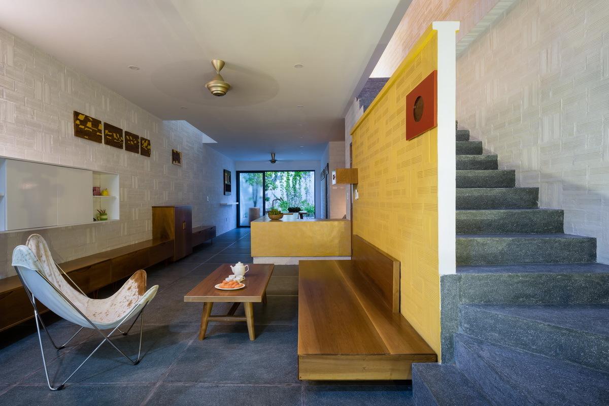 phòng khách ngôi nhà có thiết kế đơn giản với phản gỗ gắn tường, bàn gỗ nhỏ