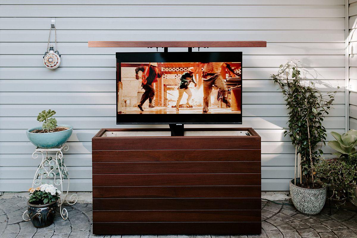 hình ảnh tivi đặt trên tủ gỗ óc chó, hai bên là cây xanh hoa cỏ trang trí