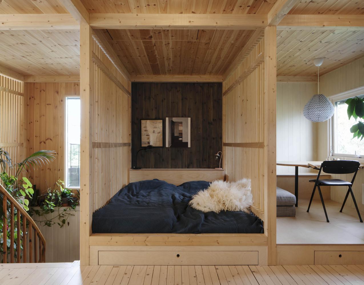 hình ảnh cận cảnh phòng ngủ trong khối gỗ ép, cạnh đó là khu vực bàn làm việc thoáng sáng