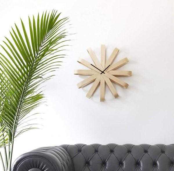 đồng hồ treo tường bằng gỗ ấn tượng, phía dưới là ghế sofa da màu đen, cạnh đó là chậu cảnh xanh tốt