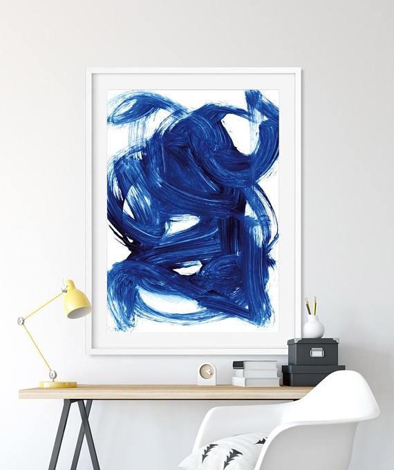 hình ảnh cận cảnh bức tranh màu xanh lam treo tường, phía dưới là bàn ghế, kệ nổi