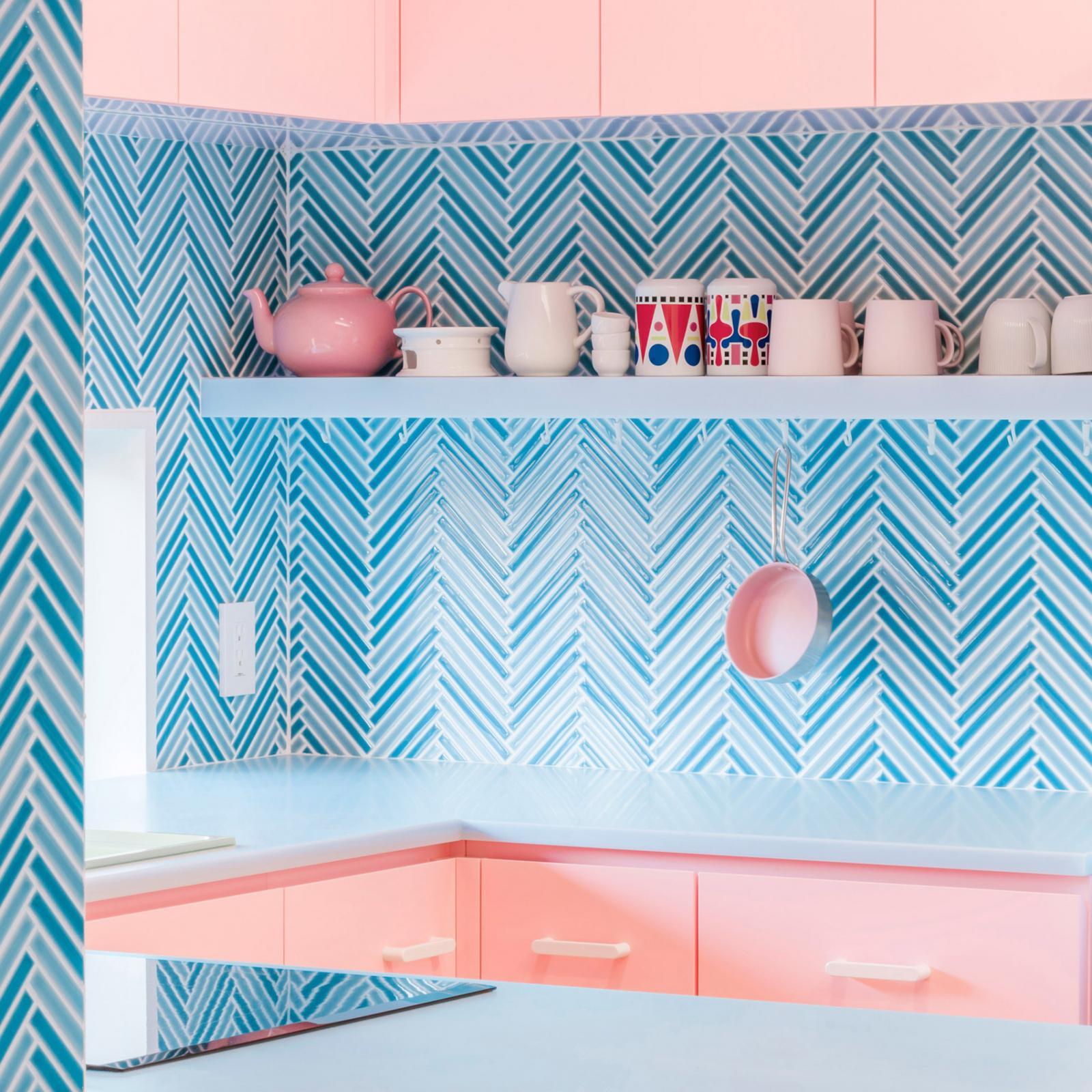 phòng bếp với tường ốp gạch màu xanh lam họa tiết xương cá, tủ màu hồng pastel