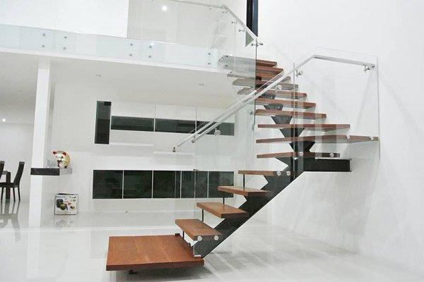 hình ảnh cận cảnh cầu thang gỗ bậc hở, lan can kính cường lực trong suốt