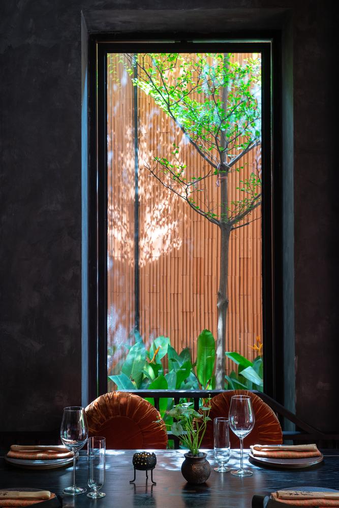 cận cảnh bàn ăn trong nhà hàng chay với khung cửa sổ mở ra sân vườn bên ngoài