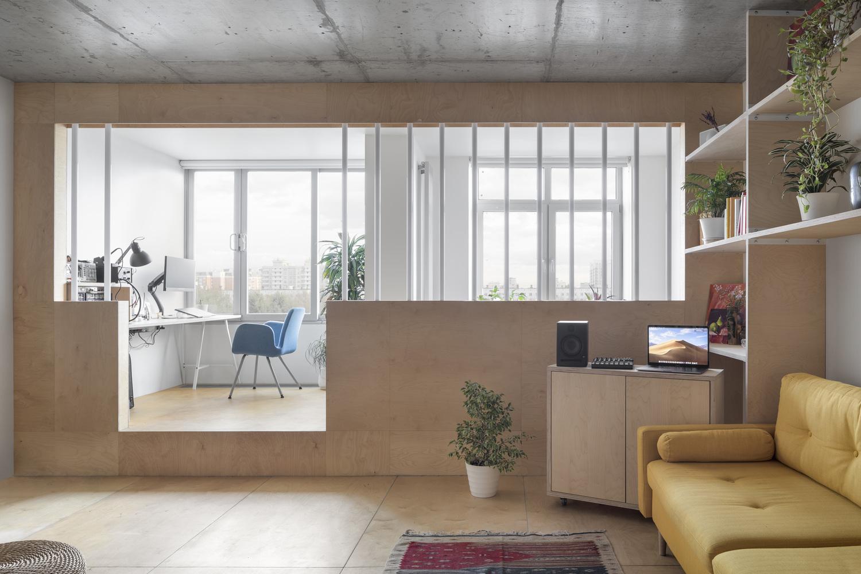 hình ảnh một góc phòng khách nối liền với góc làm việc trên bục gỗ dán