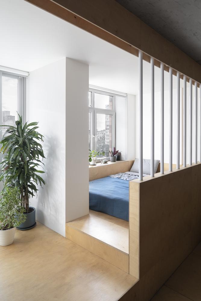 góc phòng ngủ trong căn hộ nhỏ với giường bệt, ga gối màu xanh