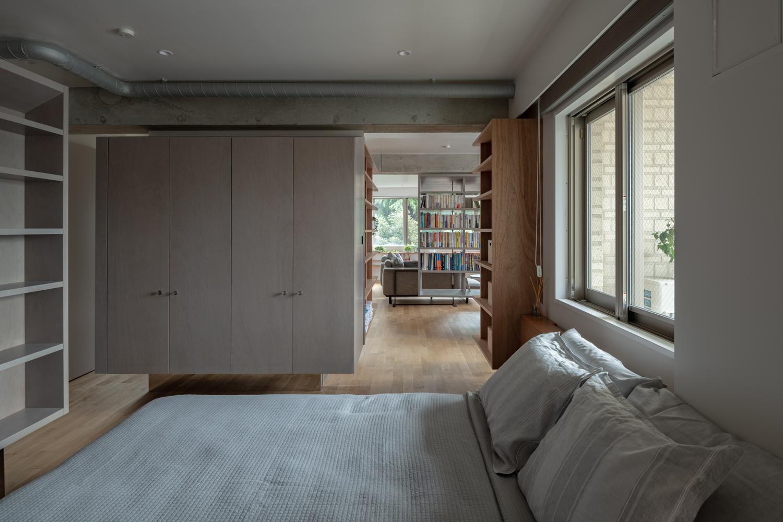 hình ảnh toàn cảnh phòng ngủ với nội thất màu trắng xám chủ đạo, cửa thông ra phòng khách, phòng đọc sách bên ngoài