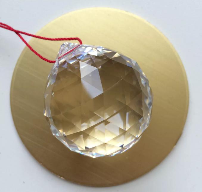 hình ảnh cận cảnh quả cầu pha lê trong suốt, nhiều mặt với dây treo màu đò
