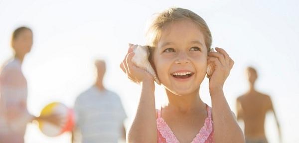 hình ảnh bé gái cầm ốc biển áp sát vào tai