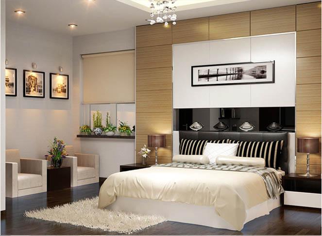 hình ảnh phòng ngủ master với giường lớn đặt giữa phòng, cạnh đó là hai ghế tựa, bàn trà, tranh treo tường, tab đầu giường bố trí đối xứng hai bên