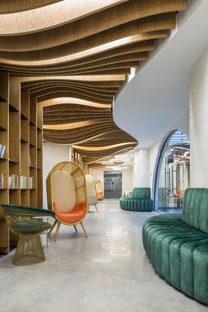 hình ảnh khu vực nghỉ ngơi dành cho nhân viên với ghế xích đu màu cam, ghế sofa mô đun màu xanh ngọc lớn, trần gỗ uốn lượn nhẹ nhàng