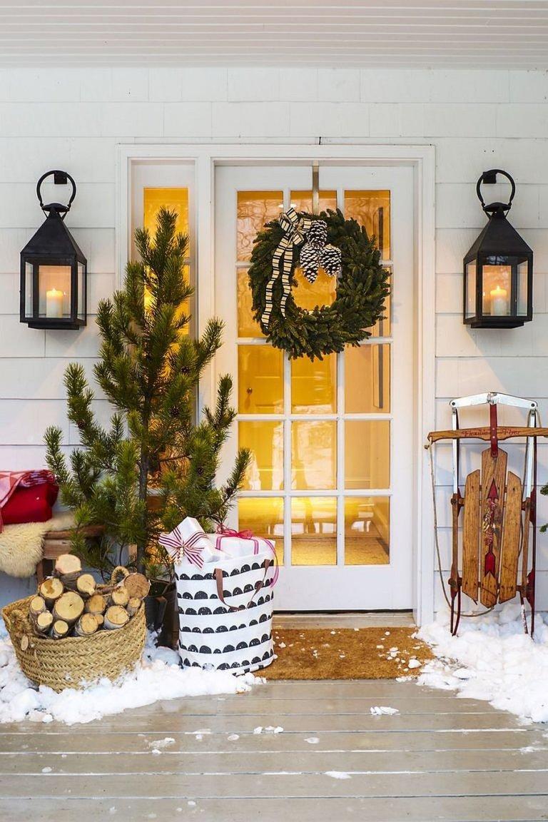 Hình ảnh cận cảnh lối vào với vòng lá xanh treo trên cửa kính, cây thông Noel bên cạnh