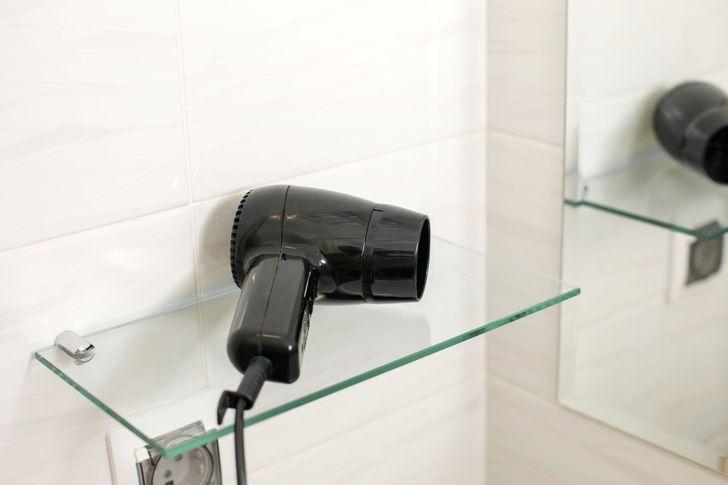 hình ảnh cận cảnh máy sấy tóc màu đen đặt trên kệ kính phòng tắm