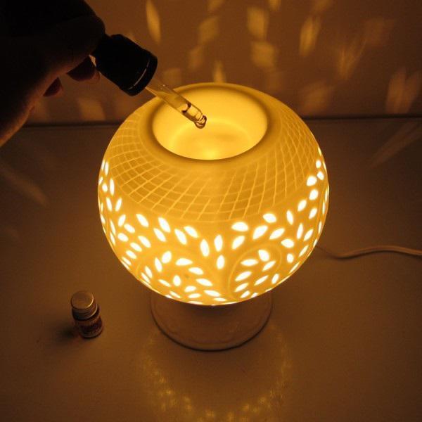 hình ảnh cận cảnh đèn xông tinh dầu hình tròn, cắt khoét lỗ hình lá, ánh sáng vàng ấm áp