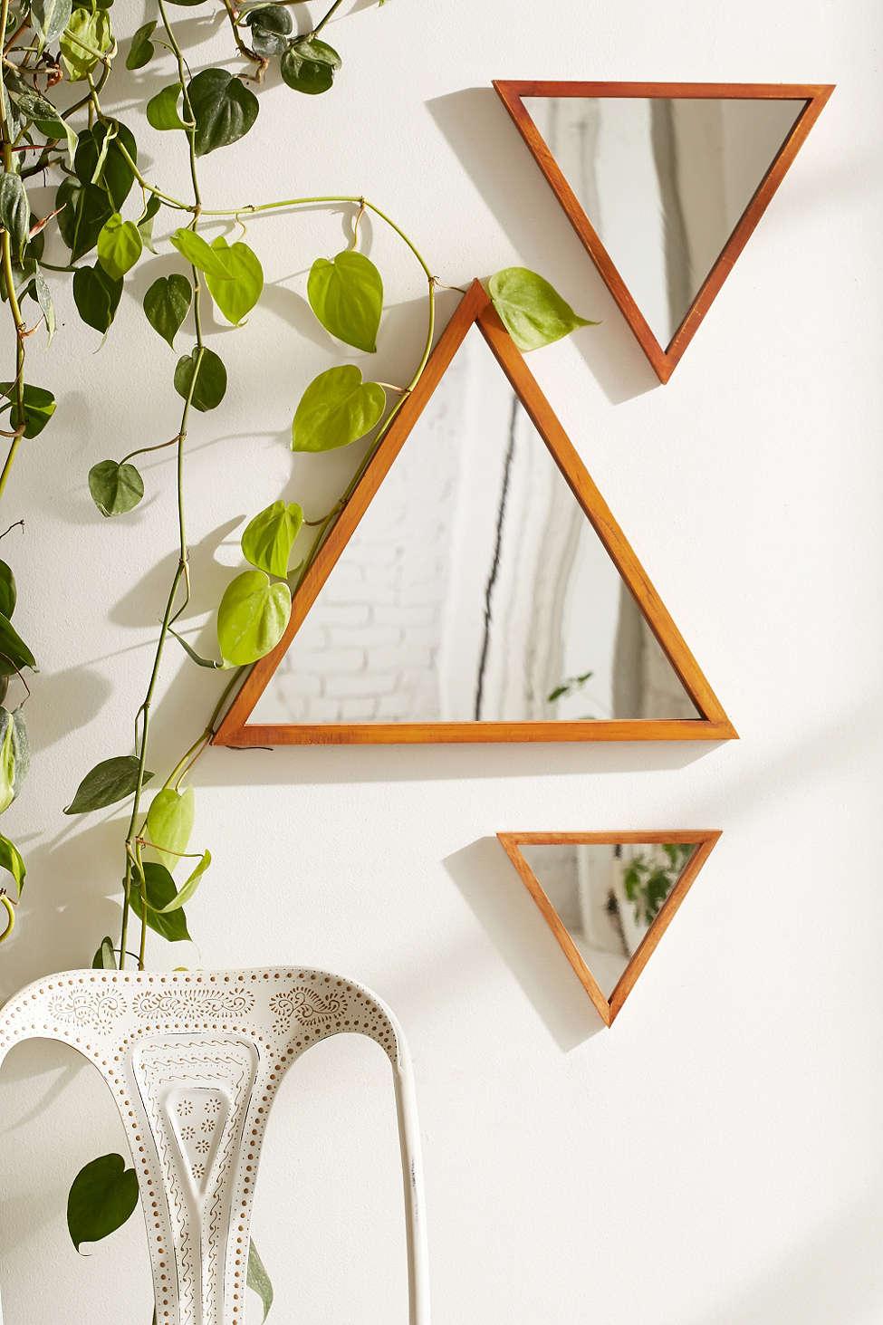 hình ảnh gương kim tự tháp treo tường với cây trầu bà leo bên cạnh