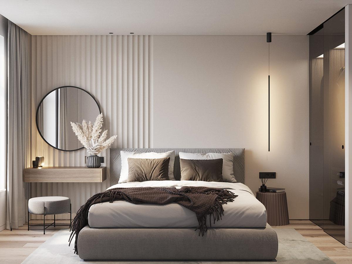 hình ảnh phòng ngủ màu kem chủ đạo, giường nệm màu xám, đèn thả màu đen, gương tròn trang điểm, vách thạch cao đầu giường có gân