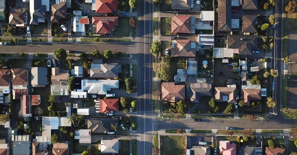 hình ảnh một khu dân cư đông đúc nhìn từ trên cao với những ngôi nhà thấp tầng mái ngói đỏ, đen, xám, giao lộ chữ T