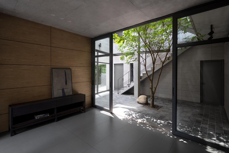 hình ảnh góc phòng khách với cửa kính lớn mở ra sân trong nhà 3 tầng