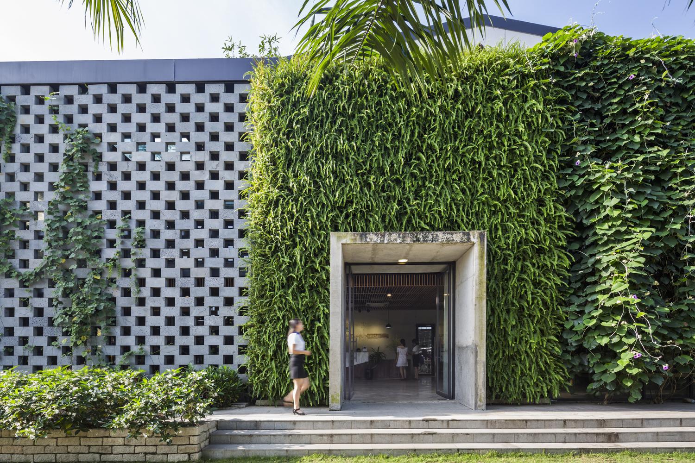 hình ảnh cận cảnh mặt tiền nhà xưởng với tường gạch lỗ màu xám, cây dây leo phủ kín cổng vào