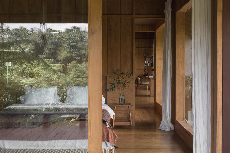 Tường kính phòng ngủ phản chiếu khung cảnh thiên nhiên, đây là cách gián tiếp mang sắc xanh của cây lá vào không gian sống.