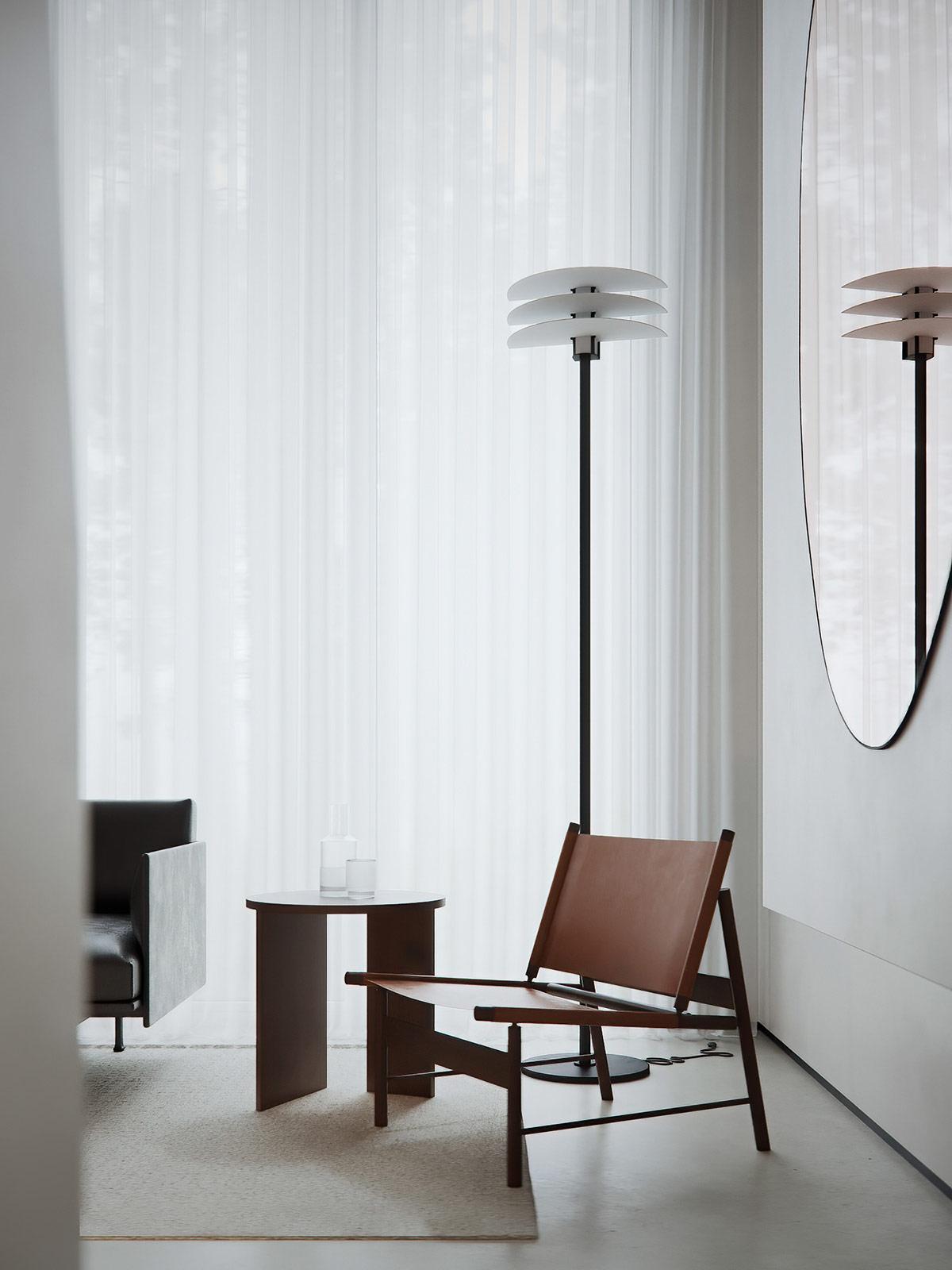 Góc đọc sách trong phòng khách được thiết kế theo phong cách thời thường với ghế dài màu hạt dẻ, đèn sàn bắt mắt, bàn phụ nhỏ.