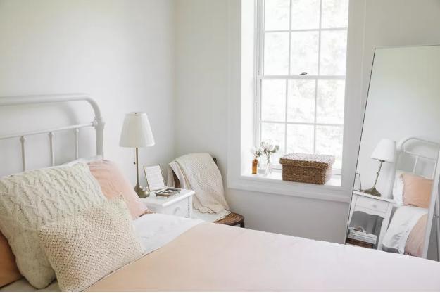 hình ảnh phòng ngủ với tường màu trắng, cửa sổ kính, gương đặt đối diện giường