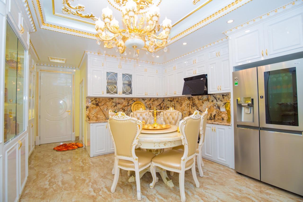 hình ảnh phòng ăn với nội thất dát vàng, bàn ăn tròn, đèn chùm trang trí, tủ lạnh xám