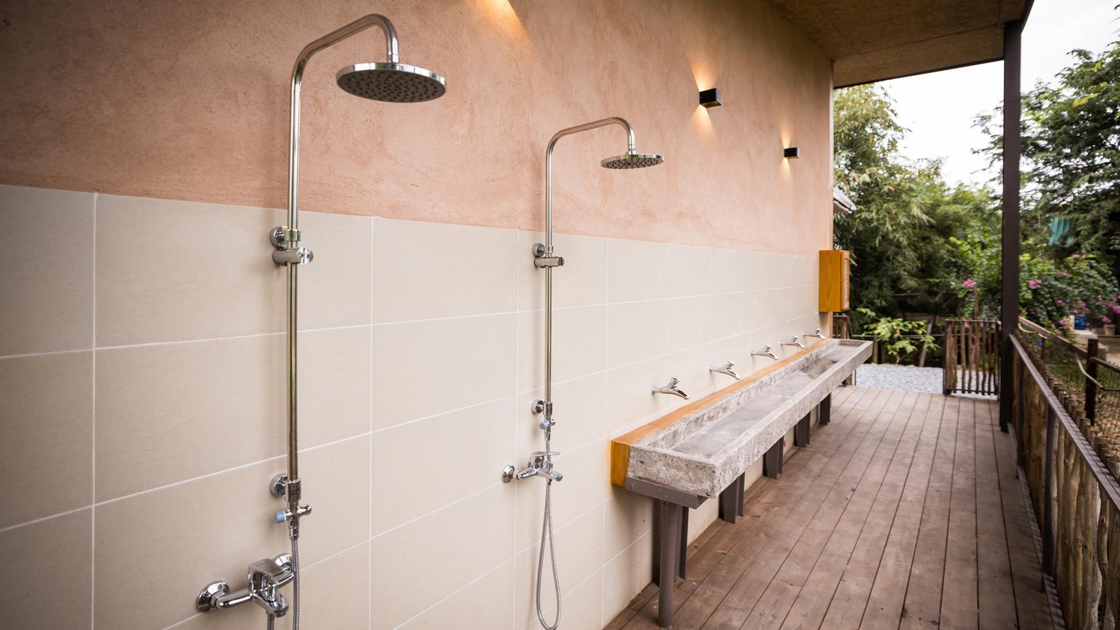 hình ảnh cận cảnh nhà vệ sinh với vòi sen trên cao, bồn rửa dài