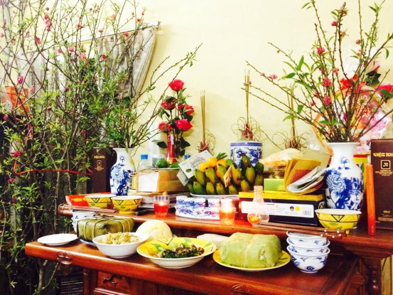 hình ảnh bàn thờ gia tiên ngày Tết với cành đào nở hoa, mâm ngũ quả, bánh chưng