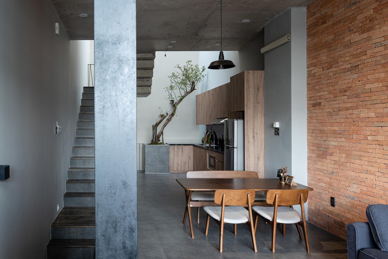 hình ảnh phòng ăn trong nhà ống với bộ bàn ghế gỗ mộc mạc, cầu thang bê tông, cây xanh trồng ở giếng trời