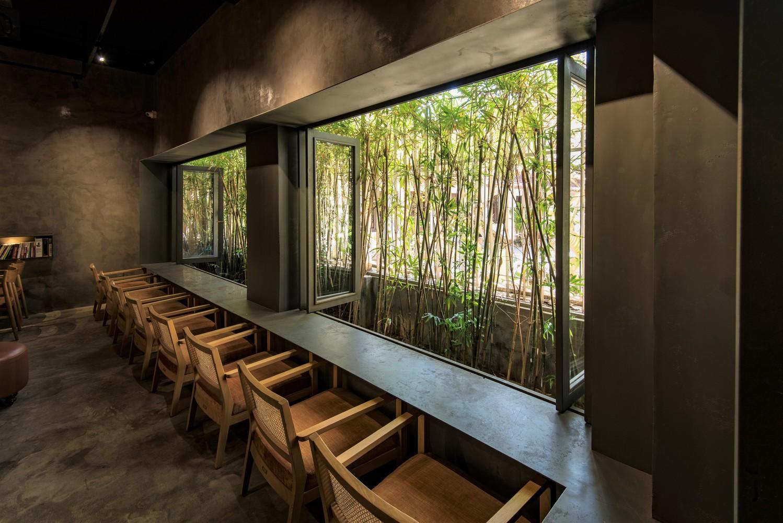 hình ảnh chỗ ngồi uống cà phê với dãy ghế gỗ sáng màu, hướng nhìn ra khu vườn xanh mát bên ngoài