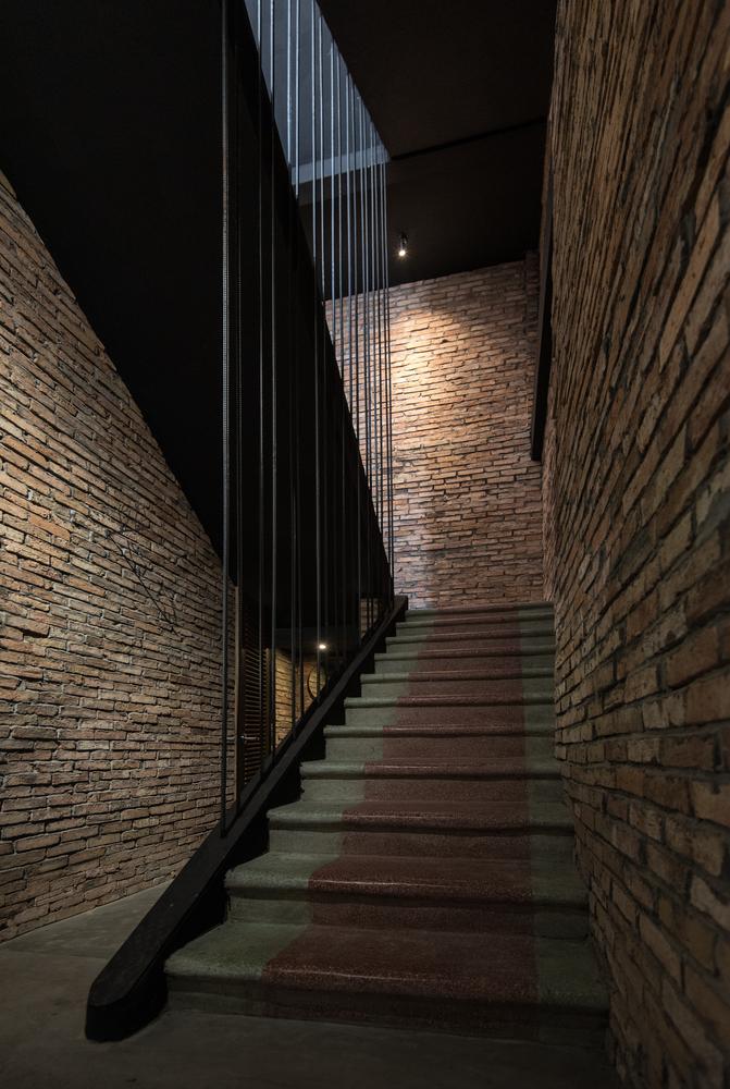 Tường gạch trần tông màu ấm áp tạo cảm giác gần gũi, thân thiện.