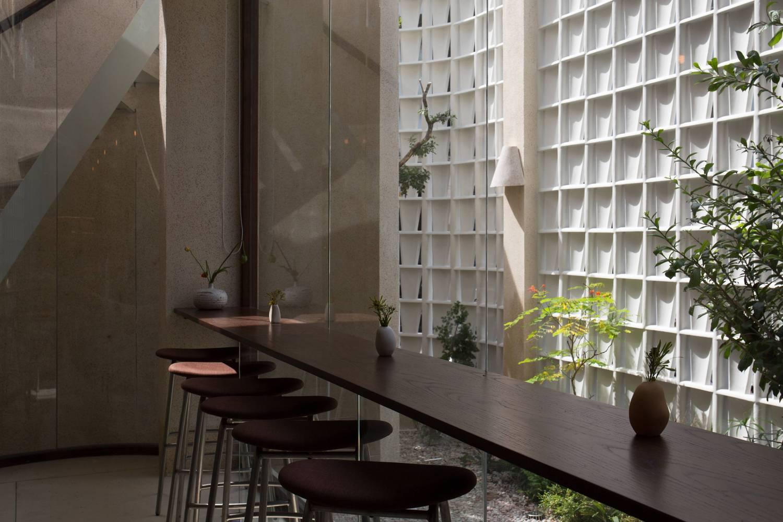 Góc thưởng thức cà phê thú vị với bàn gỗ dài, ghế bar cao thoáng.