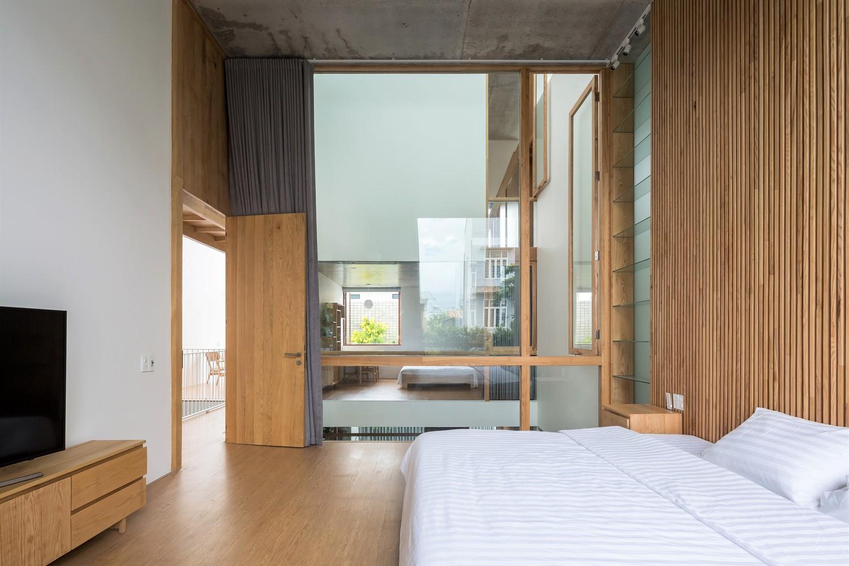 Tường kính trong suốt giúp mở rộng không gian phòng ngủ một cách trực quan.
