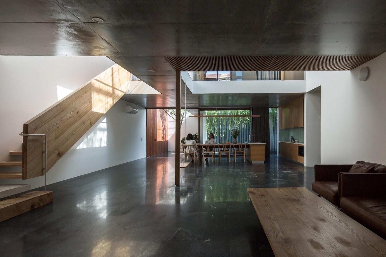hình ảnh phòng khách liên thông phòng bếp, trần bê tông, cầu thang gỗ